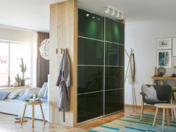 Dark green wardrobe with sliding doors used as a room divider between a bedroom and living room.