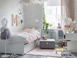 Children's bedroom with white walls with black spots and a white bed with pale pink bedding.