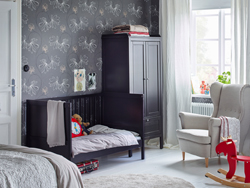 Black brown cot, wardrobe and nappy changing table in the corner of a large adult bedroom with grey patterned wallpaper.
