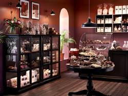 A chocolaterie with black stained cabinets with glass doors and brown walls.
