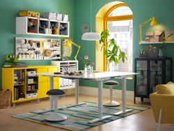 A green, white and yellow workspace with two white height adjustable desks back-to-back in the centre of the room.