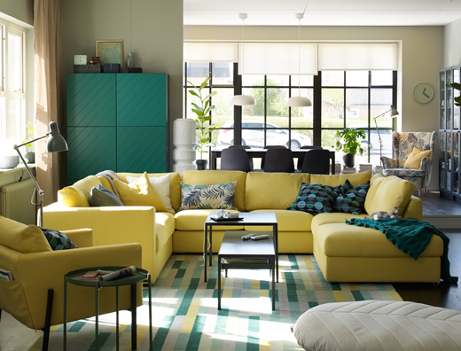 Large u-shaped yellow sofa in the centre of an open plan living and dining room.