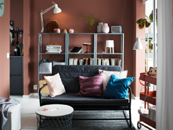 A small dark grey-black sofa in a living room setting with dark red walls and shelves across the back wall.
