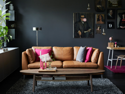 Natural leather sofa with pink and grey cushions in a living room with dark grey walls.