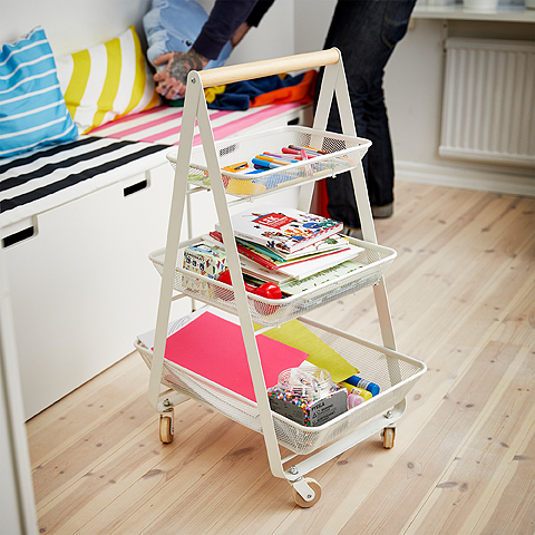 A white trolley with three baskets filled with coloring pencils, books, and paper.