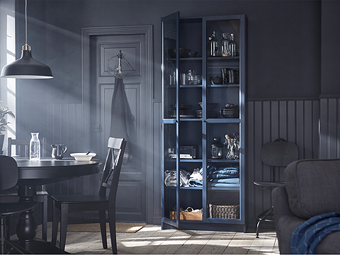 A tall BILLY bookcase makes the most of your wall height instead of using precious floor space. It also becomes a home for wine glasses, blankets, a coffee pot and more. The dark blue color and the glass doors make a fresh, modern style statement.