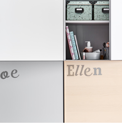 A BESTÅ storage combination with doors in different colors, decorated with sticker letters.