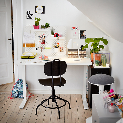 A study corner featuring a white height adjustable desk  and a black swivel chair.