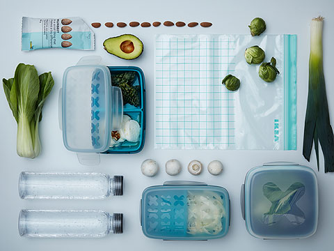 Green vegetables and nuts in various clear storage containers including zip lock bags, plastic boxes and water bottles.