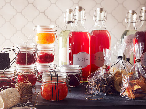 An assortment of glass storage jars and bottles containing red preserves beside homemade treats in plastic wrapping.