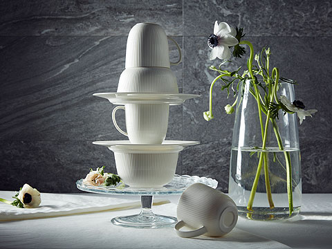A stack of white porcelain balacned on a glass cake stand next to flowers in a clear glass vase.