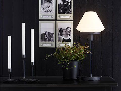 A black plant pot, candlesticks with white candles and a black and white table lamp stand in front of a black wall with framed black and white pictures.