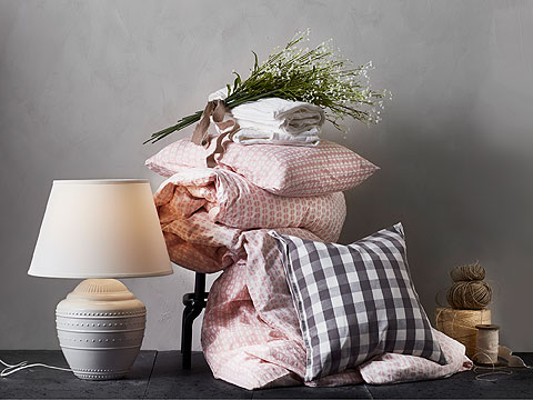 Pile of patterned pink, white and grey bedding beside a white table lamp.