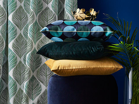 Pile of yellow, green and spotted cushions in front of blue wall and curtain with leaf motif.