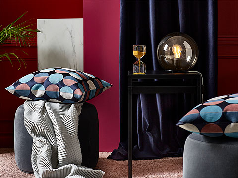Living room setting with two grey poufs and spotted cushions with dark blue curtain and dark red wall behind.