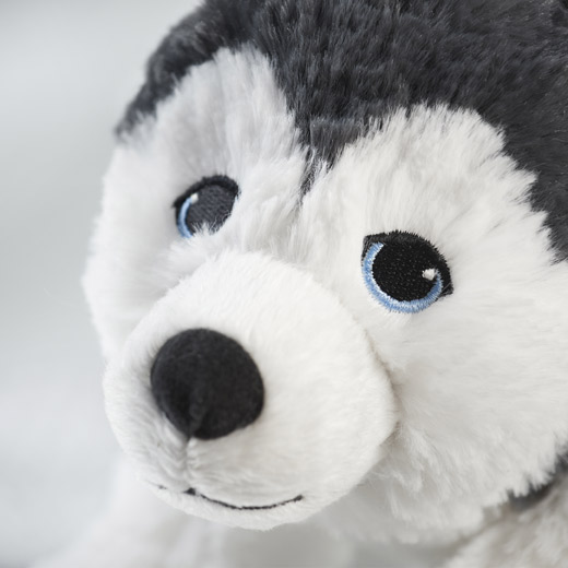 Close-up picture showing IKEA LIVLIG soft toy dog in the shape of an Siberian husky with charming blue embroidered eyes. Using embroidered eyes in all our soft toys makes these cuddly friends both safer and more characteristic.