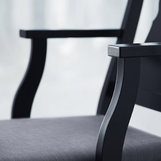 Close-up picture showing IKEA INGATORP black chair with armrests. The chair has shorter armrests than may be expected, making it fit well under the table and still offer a relaxed seating position.