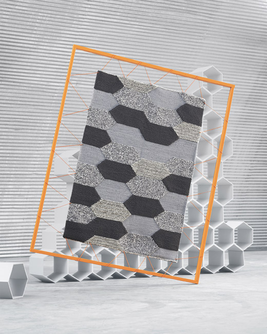 The IKEA KOLLUND wool rug has a hexagonal pattern in various grey colours. The rug is handwoven with different threads and with loops that create various heights in the pattern.