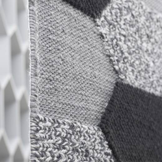 Close-up picture showing IKEA KOLLUND wool rug with a hexagonal pattern in various grey colours. The rug is handwoven in different pile heights, that gives a nice tactile experience underfoot.