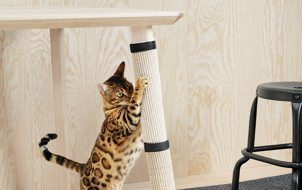 Spotted cat using its scratch pad that is wrapped around a table leg.