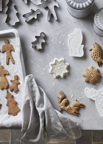 BAKGLAD pastry cutters with gingerbread holiday shaped cookies, displayed on table together.