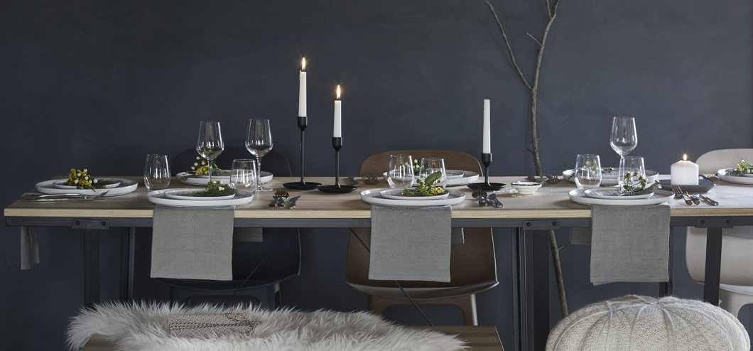 Winter table setting with white plates and black candle holders, featuring the VÄSSAD dining table.