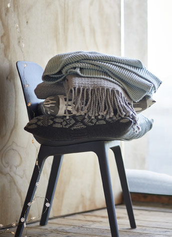Many throws and cushions stacked on a chair.