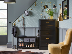 Brass coloured KÄMPIG hooks, a black PINNIG bench and UNDREDAL chest of drawers provide a place for shoes, hats, coats and smaller items in a make-shift hallway by the stairs. Gray wallpaper and walls add a cosy touch.