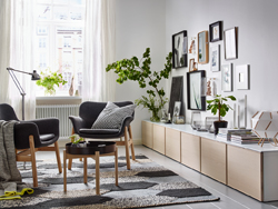 Create a smart way to display and hide-away things in your living room with a long row of low BESTÅ shelf units in white and ash. Two VEDBO armchairs in Gunnared gray and a coffee table have been placed in the center of the room.