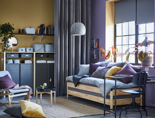 A yellow and purple studio apartment with a practical pine UTÅKER sofa bed which can be used as a sofa, single, double or twin beds. The gray and wood IVAR storage  can be seen in the background.