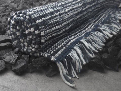 Close-up picture showing IKEA KÖPENHAMN wool rug that has a striped pattern in various grey colours and with decorative long fringes. Each rug is unique because it has been handwoven by skilled craftspeople.