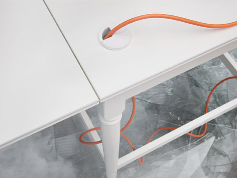 Close-up picture showing IKEA INGATORP white desk in a traditional design with a cable management hole that makes it smooth to work with electronic devices.