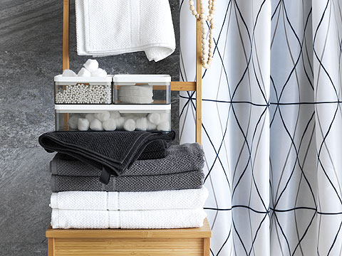 Bathroom setting with stack of grey, white and black towels, and clear storage boxes on a wooden chair and patterned shower curtain behind.