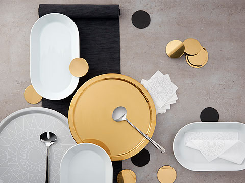 White oval dishes and a brass and light grey circular tray surrounded by brass coasters.