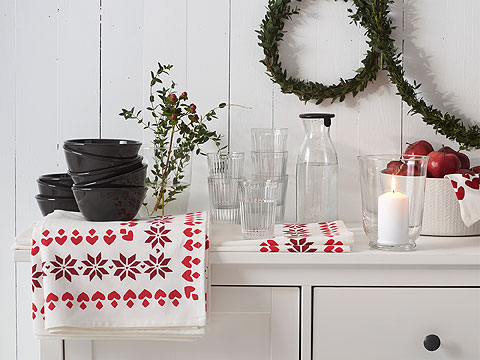 A white wood panelled wall with two green wreaths behind a white dresser with black bowls, clear glasses, a candle and a red and white tablecloth.
