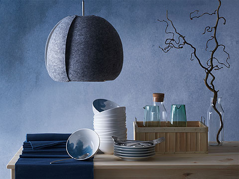 A wooden table with a pile of white bowls and dark blue table mats under a grey felt lamp.