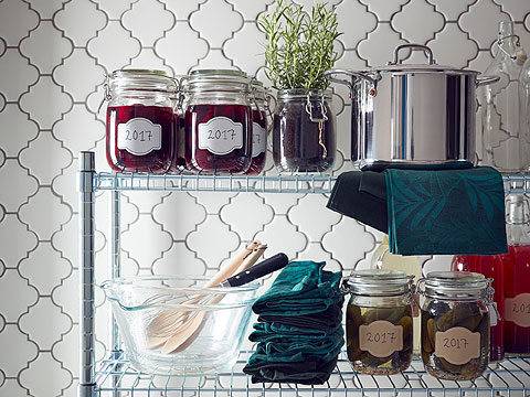 Glass storage jars and bowls, blue napkins and a saucepan on wire shelving against a wall with white tiles.