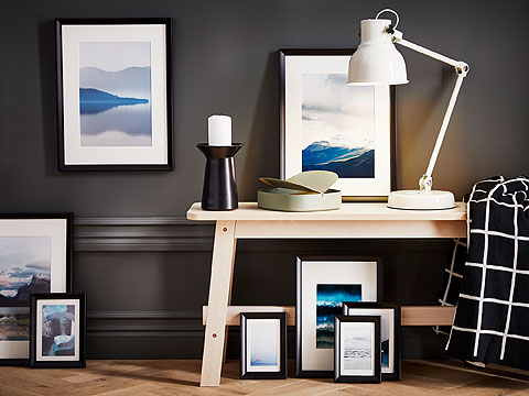 Wooden table with white angled lamp surrounded by framed landscapes against a dark grey wall.
