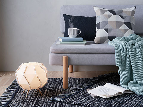 Grey sofa with light blue blanket, patterned cushion and a stack of books next to a glowing floor lamp and striped grey rugs.