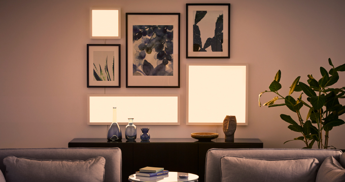A living room wall filled with picture frames and lit LED light panels, in different sizes.