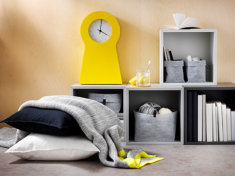 Two cushions covered with a light grey blanket with yellow trim in front of box shelves with felt storage and a yellow clock.