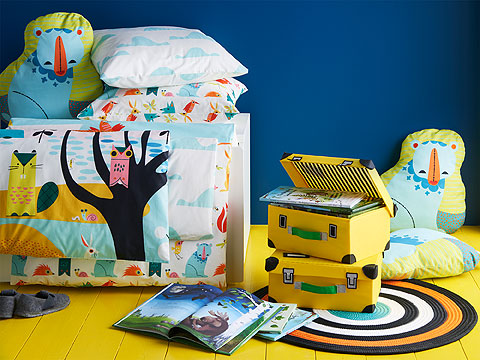 Children's bedding with colourful creatures in a setting with a bright yellow floor and blue walls.