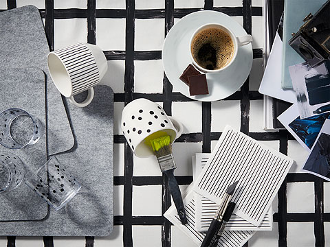 Plain, striped and spotted black and white cups beside grey felt table mats on a black and white checquered surface.