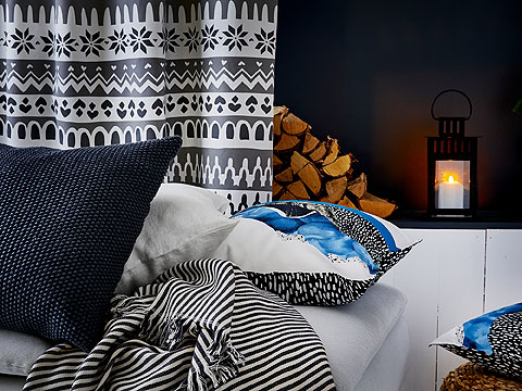 A dark grey, white and blue, white and black cushion in front of a patterned white and grey curtain and stacked fire wood.