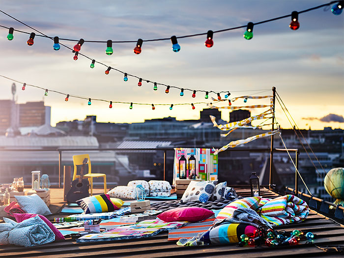 Rooftop with mult-coloured string lights, and colourful pillows and blankets.