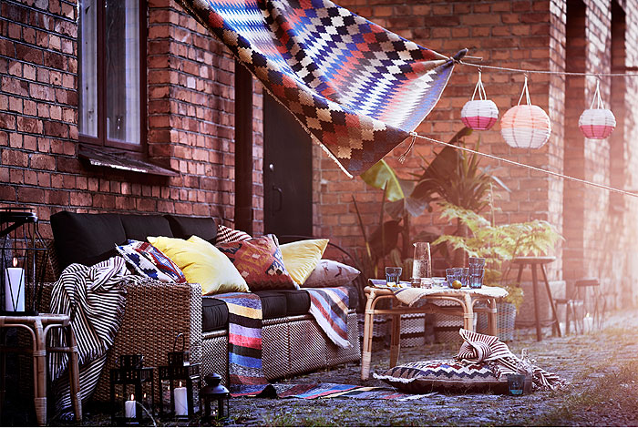 Outdoor living space decorated with colourful textiles.