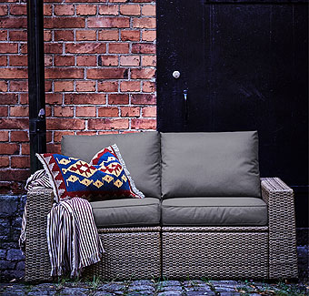 Dark grey and brown outdoor sofa decorated with colourful pillow and throw.