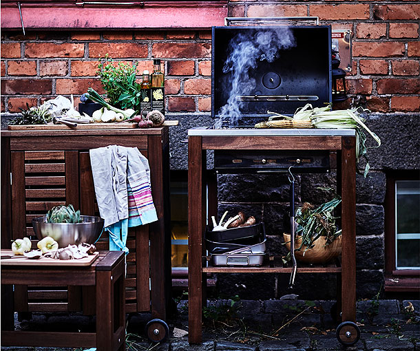 Outdoor charcoal barbecue with food prep and vegetables nearby for cooking.