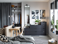 Anthracite NORDLI chest of 9-drawers against a back wall in a small living space with a sofa bed and desk.
