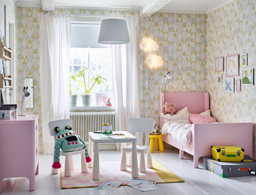 A pink, white and yellow children's bedroom with extendable BUSUNGE bed in light pink to one side and white MAMMUT tables and chairs in the center.